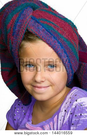 A sweet young girl with a towel wrapped around her hair after a shower. She has a nice expression with a close mouth smile.