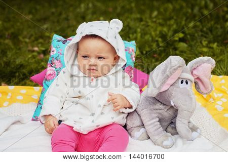little girl sitting in the park with elephants