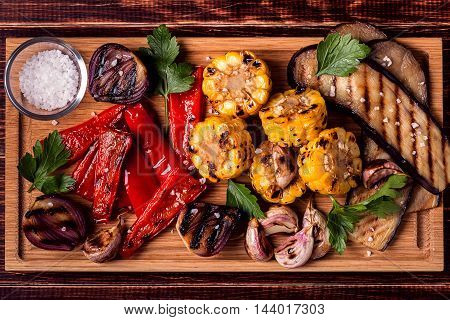Grilled vegetables on cutting board top view.