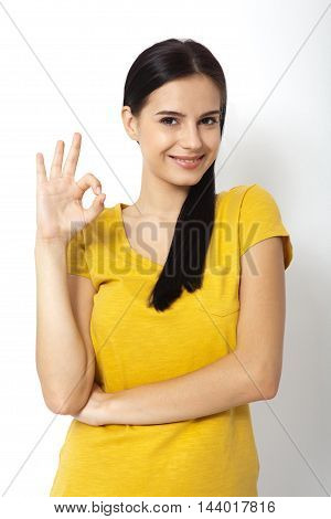 Happy young woman shows a sign okay. Success. Isolated over white background.