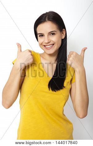 Happy attractive young woman showing thumbs up okay close up. Isolated