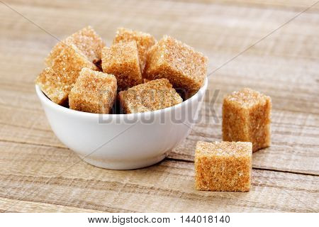 Cubes of brown sugar in bowl on wooden table