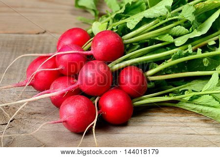 Bunch of radishes on old wooden table