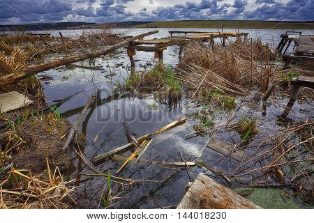 Old wooden pier with dry reed. Cloudy weather. Dramatic sky. Chaos of garbage branches and boards