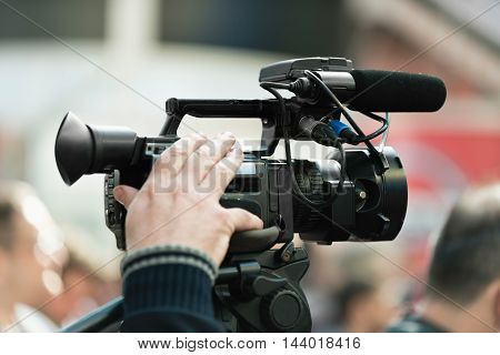 Cameraman recording a publicity event, toned image, close up, unrecognizable people