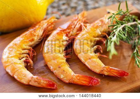 Grilled Shrimps Served on a Wooden Plate With Lemon and Rosemary. Three Grilled Seasoned Shrimps Closeup.
