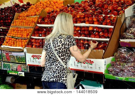 New York City - June 27 2012: Woman shopping for fresh plums at famed Fairway Market on Broadway at West 74th Street