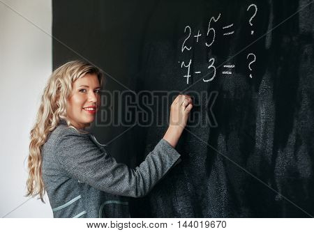 Beautiful teacher writes with chalk on blackboard examples for students. The concept of learning