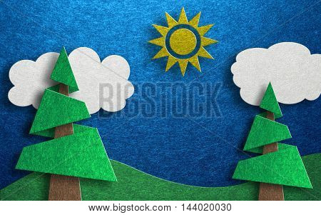 Collage made of two cutout conical shaped trees with rolling hills and clouds against a blue background and a single sun at its top center