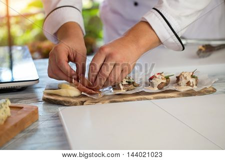 Board with pieces of meat. Man's hand touch bacon. Medallions with tasty roquefort sauce. How to serve food.