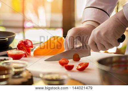Knife cuts small tomato. Bell pepper of yellow color. Cherry tomatoes for tasty soup. Be friends with health.