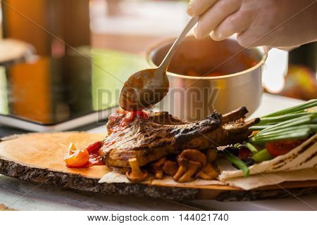 Cooked meat and vegetables. Hand with a spoon. Grilled pork with tomato sauce. Freshly cooked lunch.