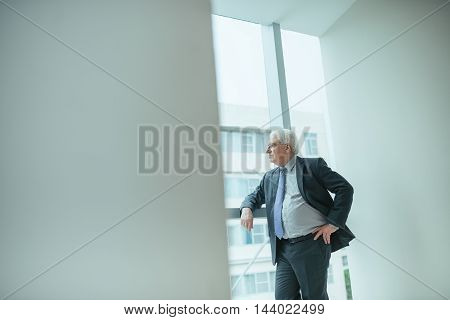 Pensive aged businessman looking through the window