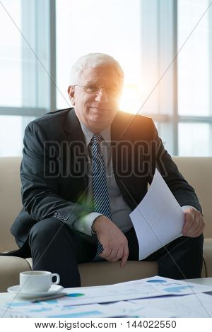 Portrait of successful aged businessman working with documents