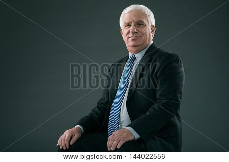Mature experienced entrepreneur smiling at camera, isolated on grey