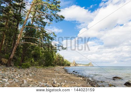 Rock-strewn shore leads to the two headlands that stick out far in the water of lake Baikal