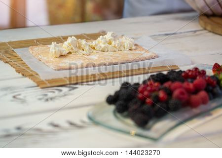 Cream cheese on dough. Bright and dark berries. Recipe of dessert with mascarpone. How to prepare sweet delicacy.