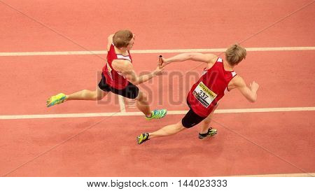 LINZ, AUSTRIA - FEBRUARY 22, 2015: Dustin Jordan Hnilicka (#337) and  Paul Schuster (#338 Austria) compete in the men's 4x200m relay event in an indoor track and field event.