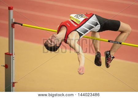 LINZ, AUSTRIA - FEBRUARY 22, 2015: Alexander Dengg (#256 Austria) competes in the men's high jump event in an indoor track and field event.