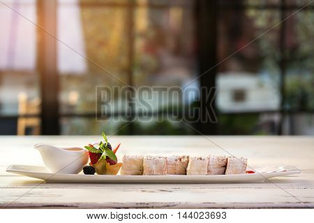 Dessert on long plate. Jug and tartlet with berries. Sweet rolls with mascarpone cheese. Appetizing dish on the table.