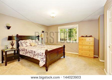Bedroom In Light Tones With Wooden Furniture And Carpet Floor.