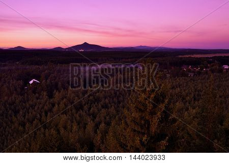 evening view to pine forests with mountains Ralsko and Jested on the horizont with huts from rocks Hradcanska vyhlidka in tourist area Machuv kraj in czech landscape