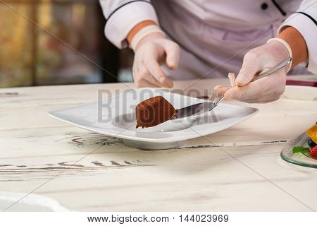 Hand holds cake on spatula. Plate on white wooden surface. Small dessert with chocolate crumbs. Sweet food in cafe.
