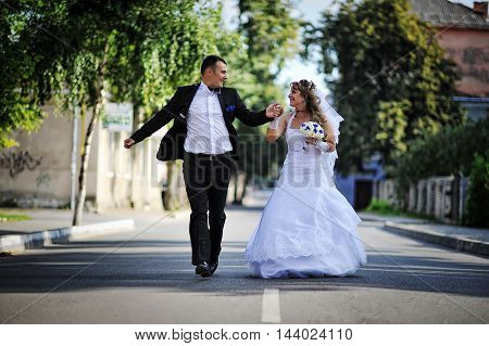 Wedding Couple Running And Have Fun On The Road