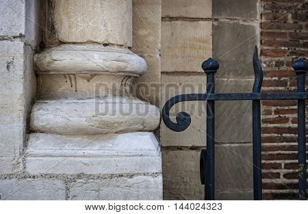 Old stone column plinth or bottom and fragment of wrought iron fence. Architectural detail of Saint Sernin Basilica, Toulouse, France.