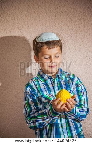 Charming boy in  white knitted skullcap is holding citrus. Citron - ritual fruit for the Jewish holiday of Sukkot