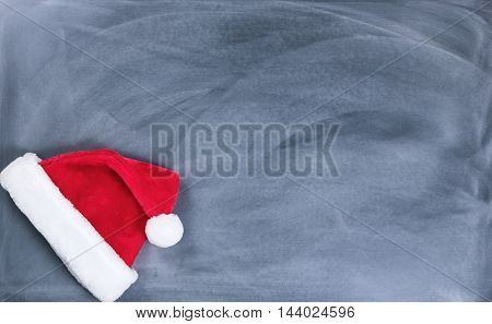 Santa cap on erased chalkboard for Christmas wish list concept.