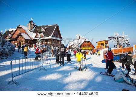 KOHUTKA, CZECH REPUBLIC - JANUARY 16, 2010: Ski resort in the Czech Tatra. Houses with peaked roofs. Skiers in bright jackets are preparing to descend on skis