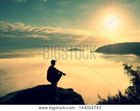 Moment Of Loneliness. Man Sit On Rock And Watching Into Colorful Mist And Fog In Valley.