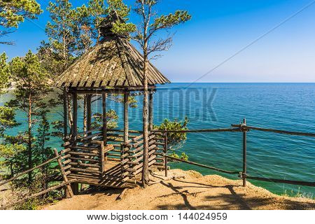 Picturesque wooden gazebo stands next to the footpath at the edge of the cliff. From it has magnificent views of lake Baikal.
