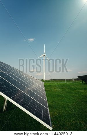 Solar panels and a windmill generate electricity from the sun. Renewable sources of energy.