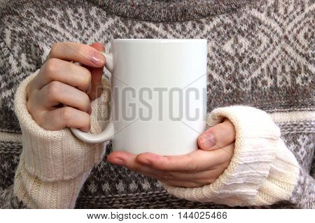 Girl in a warm sweater is holding white mug in hands. Mockup for winter gifts design.