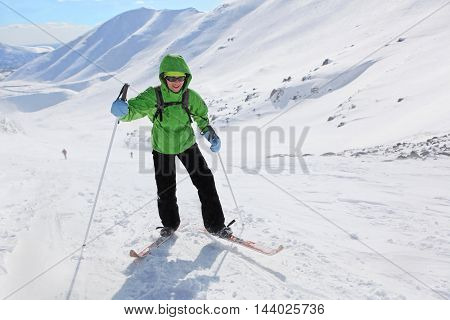 Murmansk regionRussia - April 11 2013: a young woman rises in the snowy slopes on skis in Hibiny mountains.