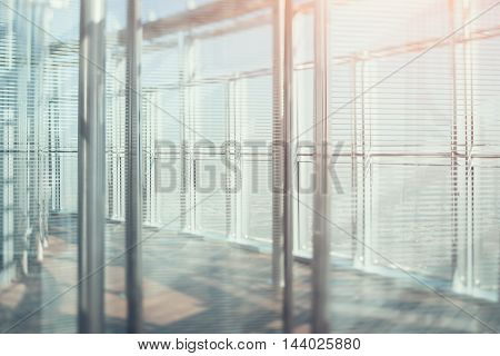 Abstract office interior background, the sun rays with flares, glass, steel columns and blinds, view from skyscraper through the window, the cityscape outside