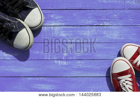 Two pairs of sports sneakers blue for men red for women on a wooden purple background top view