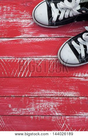 pair of blue sneakers in a corner of a shabby red background vertical composition top view