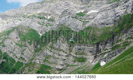 cable car before the steep rock faces of the Saentis in the Alpstein-massif in the Swiss Mountains, small snow fields,