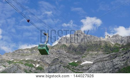 Mountain world in Switzerland, view to the mountain peak Saentis and the aerial tramway that leads to the summit, steep rock faces and small snow fields, blue sky and white clouds