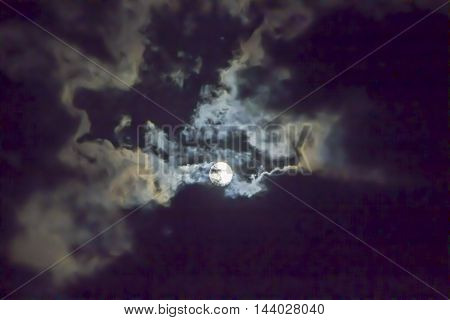 the moon in clouds in the night sky