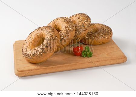 fresh bagels topped with seeds on wooden cutting board
