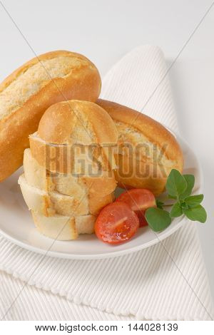 whole and sliced mini baguettes on white plate