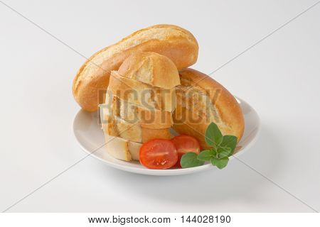 whole and sliced mini baguettes on wooden cutting board