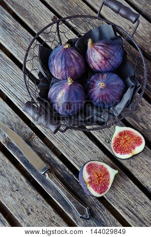 Fresh Figs in the basket on the wooden background, top view
