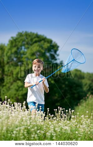 Cute happy boy with catch net against blue summer sky background. Laughing boy with butterfly net catching insects in green field. Best childhood concept.