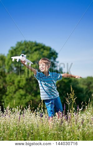 Happy kid playing with toy airplane against blue summer sky background. Laughing boy with plane in green field. Best childhood concept.