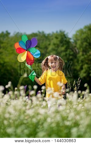 Cute happy little girl playing outdoors with windmill toy against blue summer sky background. Laughing kid in green field. Best childhood concept.